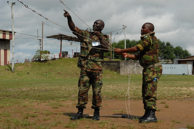 Military members from Nigeria (left) and Lesotho (right) assist in a setting up a commnications antenna, June 19, 2012, during the annual Africa Endeavor military exercise held this year in Douala, Cameroon. African Endeavor, an annual communications joint exercise sponsored by U.S. Africa Command, focuses on the interoperability of equipment and information sharing among military representatives throughout the African Union.
