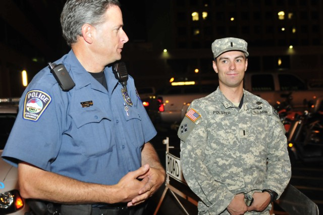 """FORT CARSON, Colo. """" Officer William Watson, Colorado Springs Police Department, arranges a ride for a Fort Carson Soldier with Courtesy Patrol Officer, 1st Lt. Greg Polster, executive officer, Troop E, 1st Squadron, 10th Cavalry Regiment, 2nd Brigade Combat Team, 4th Infantry Division, in downtown Colorado Springs, June 22, 2012. In the almost two years since its inception, the Fort Carson Courtesy Patrol provided rides to hundreds of Soldiers. Some nights only a few Soldiers take advantage of the program, other nights a dozen may be escorted home.  (U.S. Army photo by Pfc. Andrew Ingram, 4th Inf. Div. PAO)"""