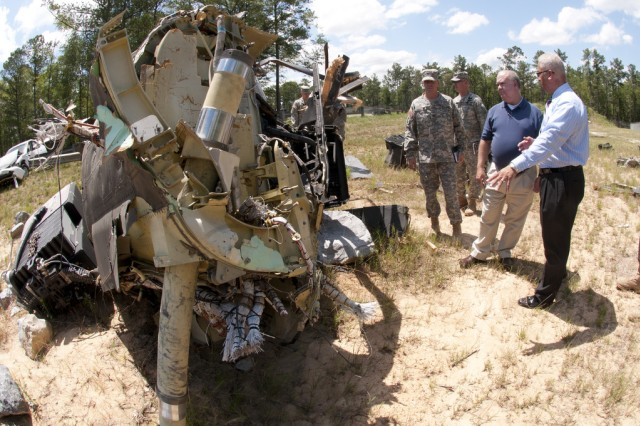 Under Secretary of the Army Joseph W. Westphal observes wreckage of an Army helicopter that is assessed at the U.S. Army Combat Readiness/Safety Center at Fort Rucker, Ala., to help avoid accidents in the future.