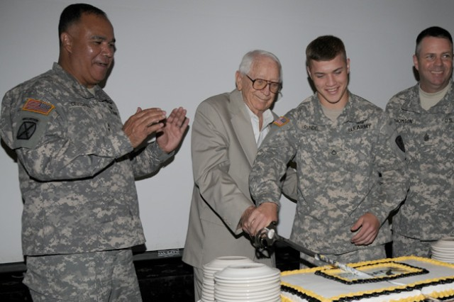 Maj. Gen. Anthony G. Crutchfield, U.S. Army Aviation Center of Excellence and Fort Rucker commanding general, applauds as retired Col. Sheldon Bailey and Pfc. Tyler Rundel cut the cake to commemorate the Army's 237th birthday June 20.