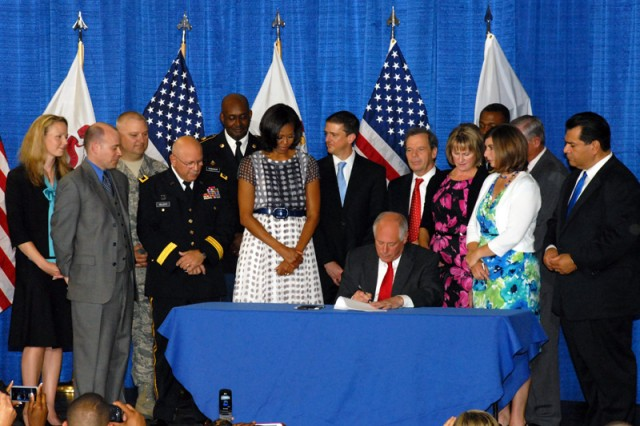 "Gov. Pat Quinn, flanked by the First Lady Michelle Obama, Acting Adjutant General of Illinois Maj. Gen. Dennis Celletti, bill sponsors Illinois State Senate President John Cullerton, state Rep. Bob Pritchard, state Sen. Martin Sandoval, and other officials, signed into law the ""Military Family Licensing Act,"" June 26, 2012, in Chicago, which will make Illinois the 23rd state to adopt pro-military spouse license portability legislation when the law takes effect Jan. 1, 2013. The bill provides for temporary expedited professional and educational licenses for active duty members of the military and their spouses after the families relocate to Illinois for military service."