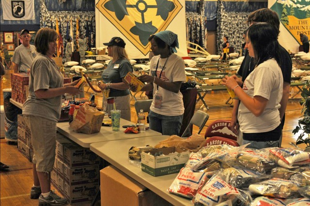 Fort Carson, Colo., volunteers from the USO and other relief organizations set up a table full of relief items to assist service members and their families displaced by the Waldo Canyon wildfire.