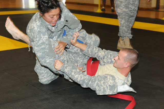 Staff Sgt. Silvia Zetino, 69th Chemical Company, takes on Sgt. Corey Abernathy, 102nd Civilian Support Team,^Weapons of Mass Destruction, in combatives during the Joint CBRN Warrior competition.