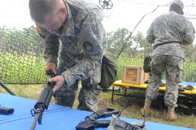 Cpl. Adam Gale and Spc. Jean Africain, 83rd Chemical Battalion, race to disassemble and assemble weapons during the Joint CBRN Warrior competition.