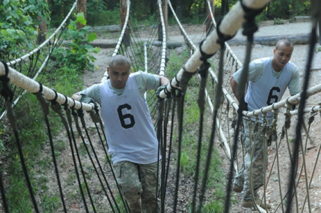 Pfc. Ryan Chavez and Staff Sgt. Jammie Camacho, 110th Chemical Battalion, cross a rope bridge at the Physical Fitness Confidence Course.