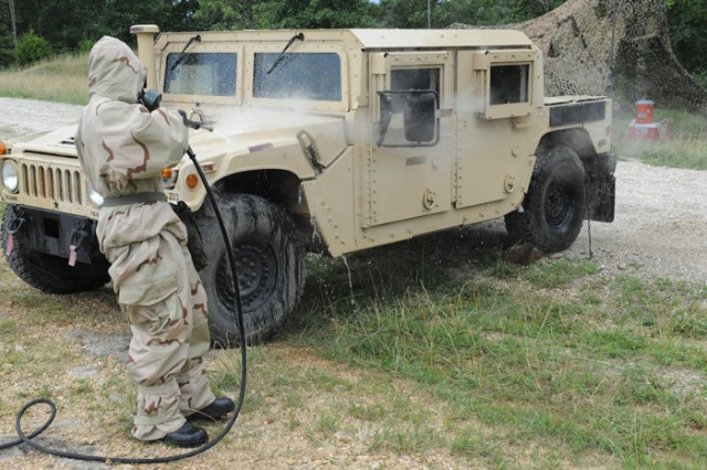 Sgt. Juan Perez, 379th Chemical Company, decontaminates a vehicle.