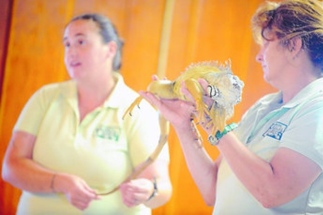 "Leslie Eicher (right), a manager at the Leesburg Animal Park in Leesburg, Va., holds Charlie, a green iguana, as Jeanne Seeley, a day manager at the park, talks about Charlie's favorite foods during the ""Reading Is Delicious"" annual summer reading program sponsored by the Medal of Honor Memorial Library on Tuesday at Burba Lake Cottage. Upcoming events include a magician in July and ""mad science"" program in August."