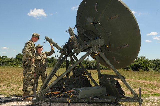 ET2 Jason Woodfin and ET2 Catherine Minard, both Naval Mobile Construction Battalion 15, discuss the deployment of the 2.5-meter satellite antenna during a command post exercise on Fort Leonard Wood June 22.
