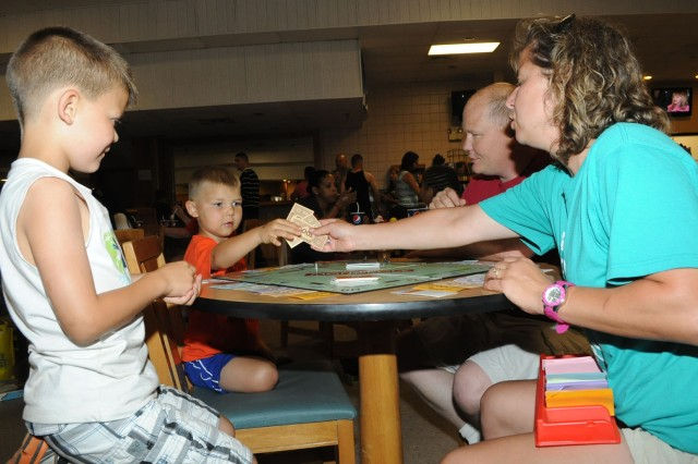 The Shepard family, from left, Sean, 7, Ian, 4, Mike and Janet, plays Monopoly at the USO Family Game Night Friday.