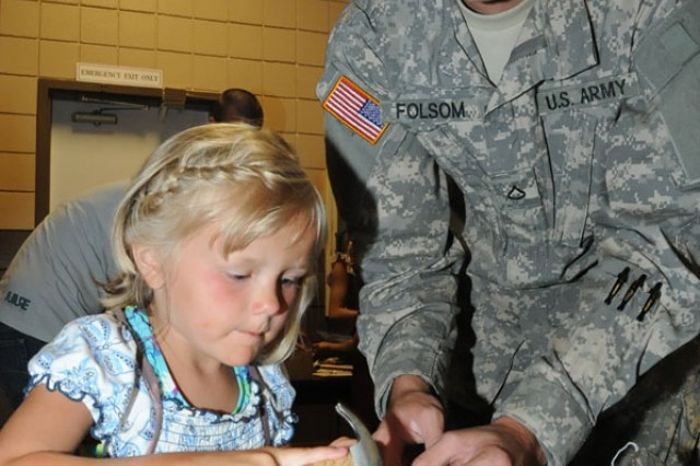 Alena Sanford, 5, builds a wooden craft with help from Pfc. Tyler Folsom, 554th Engineer Battalion, at the USO's Family^Game Night Friday.