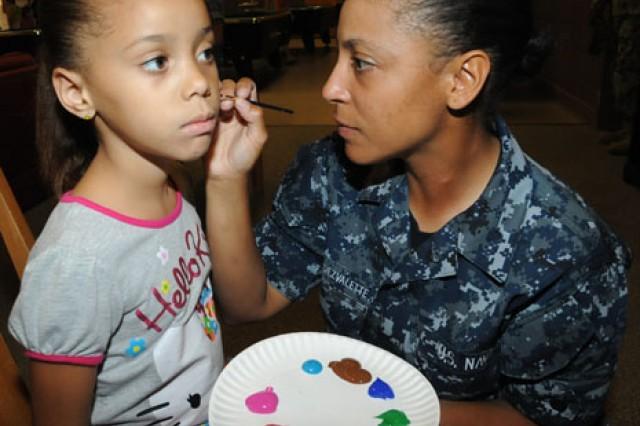 Crystal Carreras, 5, holds still while Seaman Elizabeth Hernandezvalette, CSFE, paints her face.