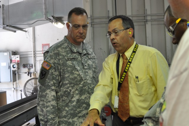 Randall Burcham, supervisory program manager (demilitarization) at Crane Army Ammunition Activity, motions to JMC Commanding General Brig. Gen. Kevin G. O'Connell, during a tour of the site's 30 mm projectile recovery line in Crane, Ind.