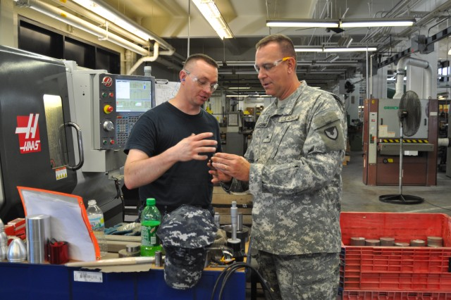 Navy Third Class Petty Officer Benjamin Hinrichs explains a manufacturing process to JMC Commanding General Brig. Gen. Kevin G. O'Connell during a tour of the Crane Army Ammunition Activity's machine shop during a June 19 visit. Hinrichs is a reservist assigned to Navy Operational Support Center Decatur, Ill.