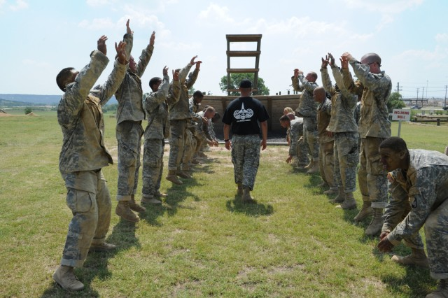 An instructor at the Air Assault School at Fort Hood, Texas, leads Soldiers through stretches, jumps and warm-up exercises before tackling an incline wall of an obstacle course June 23, 2012.