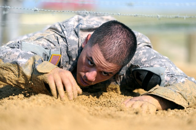 Sgt. Christopher Lopez, 1st Cavalry Division, works his way through the Low Crawl obstacle, avoiding the barbed wire overhead, June 23, 2012, on Zero Day of Air Assault School training at Fort Hood, Texas.