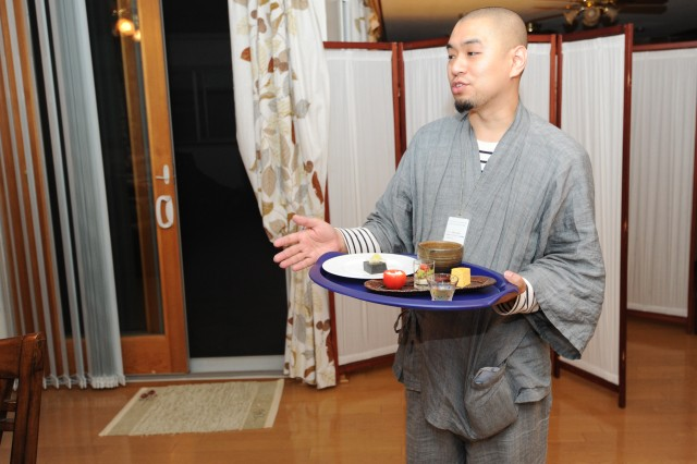 "Kaku Aoe, a Buddhist monk, explains about the dishes to the participants during ""Kurayami Gohan"".   Dark dining is based on the theory that flavors are intensified when people cannot see what they are eating. Aoe combined the idea with Buddhist principles and began offering the hybrid program at his temple in Asakusa, Tokyo."