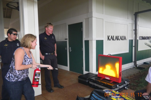 "SCHOFIELD BARRACKS, Hawaii "" Adam Chaddick, fire inspector, Federal Fire Department, instructs 1st Lt. Elizabeth Nelson on the proper way to use a fire extinguisher at Army Public Health Nursing's health fair, held June 14, at the Kalakaua Community Center, here. Nelson is using Fed Fire's new digital fire extinguisher training system, which simulates different kinds of fires and conditions. The electronic system saves money and is more environmentally friendly. Nelson is a registered nurse in Tripler Army Medical Center's Antepartum Obstetrics/Gynecology ward."