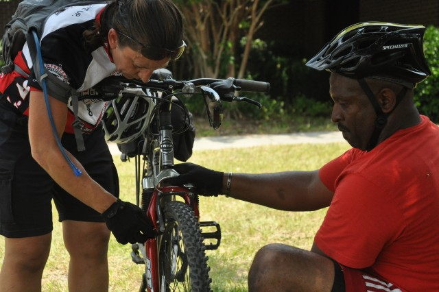 Jutkofsky assists Walter Vance, an officer with the Palmetto Health Police Department, with fixing his bike after completing a six-mile bike ride.