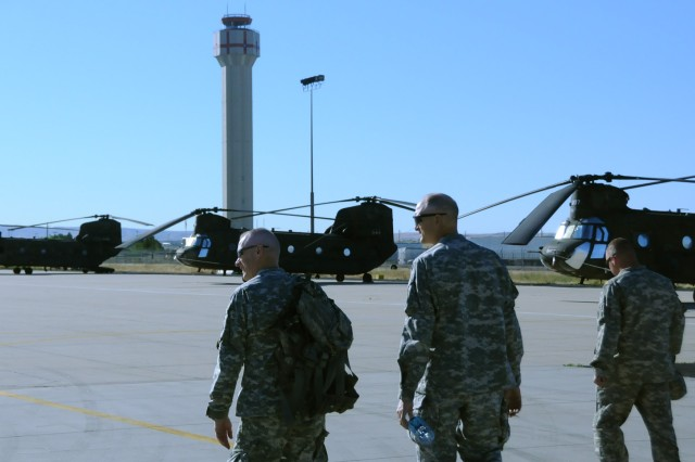 Accompanied by 1st Lt. Mike Boos, far right, the interim commander of Company B, 1/214th General Support Aviation Battalion, Brig. Gen. Pete Quinn, left, and Command Sgt. Maj. Neil Heupel, center, of the 11th Aviation Command, make their way out to the flight line and the CH-47 Chinook helicopters of B Company. Quinn and Heupel enjoyed a day of in-flight door gunnery practice and insertion/extraction rehearsal exercises in the mountains near Boise, Idaho on June 21.
