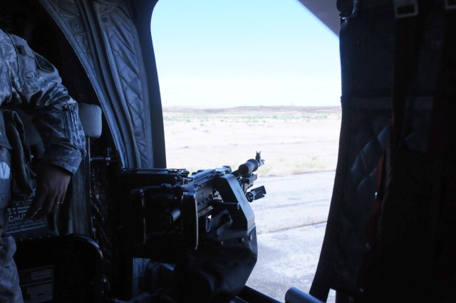 A view over the sights of an M240B machine gun mounted in the door of a CH-47 Chinook helicopter. During annual training, Soldiers of Company B, 1/214th General Support Aviation Battalion out of Fort Lewis, Wash., conducted gunnery practice in Boise, Idaho on June 21.