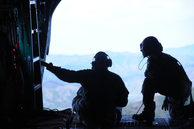 Command Sgt. Maj. Neil Huepel of the 11th Aviation Command, sits on the back of a CH-47 Chinook helicopter with crew chief Staff Sgt. Gary True of B Company, 1/214th General Support Aviation Battalion, during insertion/extraction practice near Boise, Idaho on June 21. B Company, out of Fort Lewis, Wash., was conducting annual training, which also included door gunnery with the M240B machine gun.
