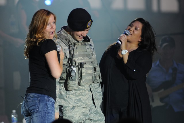 "A reluctant Senior Airman Zachary Villano from the 354th Security Forces Squadron, Eielson Air Force Base, endures an unexpected serenade by Julie Dutchak (left) and Mari Anne Jayme as they sing to him Aretha Franklin's ""A Natural Woman."" (Photo by Brian Schlumbohm, Fort Wainwright PAO)"