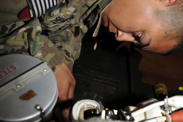 Corporal Noel Esperza, a UH-60 Black Hawk crew chief with Company D, 2nd Battalion, 25th Aviation Regiment, 25th Combat Aviation Brigade, and a native of Sherman, Texas, installs safety wire on a hydraulic hand pump filter on a UH-60 Black Hawk helicopter during a phase maintenance session on Forward Operating Base Wolverine, Afghanistan, June 12.
