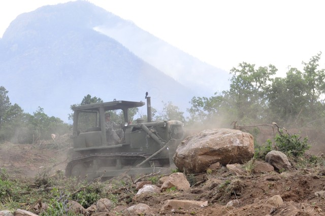 Sgt. 1st Class Justin Payne, horizontal construction engineer, 576th Engineer Company, 4th Engineer Battalion, uses a Caterpillar D7F bulldozer to clear a firebreak during efforts to contain the Waldo Canyon Fire at the U.S. Air Force Academy in Colorado Springs, Colo. The engineers built the firebreak to prevent flames from moving from the academy into the residential area across the fence. During the first 72 hours of their mission, engineers cleared more than 12 miles of land.