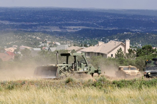 Fort Carson Soldiers, assigned to 52nd and 4th Engineer Battalions, assist efforts to contain the Waldo Canyon Fire at the U.S. Air Force Academy in Colorado Springs, Colo. The engineers used bulldozers and support vehicles to create strips of cleared earth called firebreaks, ranging from eight to 100-feet wide, to stop the wildfire's progress.