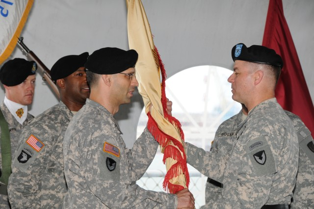 PEARL HARBOR, Hawaii - Brig. Gen. Theodore Harrison, commander, U.S. Army Expeditionary Contracting Command hands the 413th Contracting Support Brigade flag to Col. Martin Zybura, incoming commander, signifying the brigade's first official change of command.