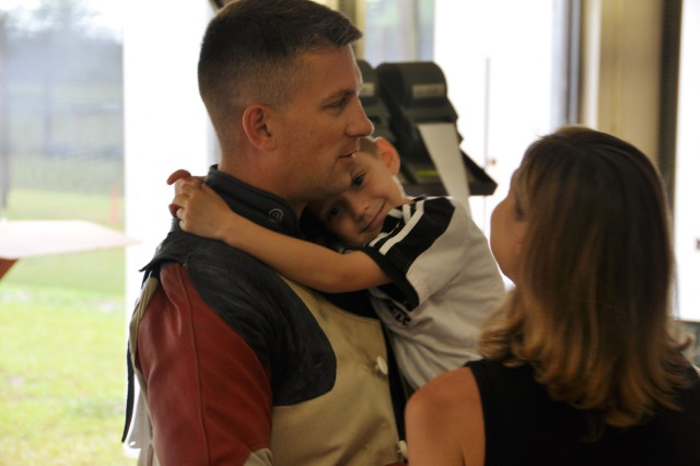 Sgt. 1st Class Jason Parker, U.S. Army Marksmanship Unit, is greeted by his youngest son, Wyatt, and wife, Andrea, June 11, 2012, at Pool Range on Fort Benning, Ga. Parker will compete at the London Olympics, his fourth time making the Olympic team.