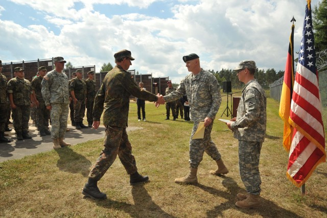 The German team leader of a tri-nation team shakes hands with Col. Adam Loveless, chief of training at the Joint Multinational Training Command during the first day of the 2012 Tri-Nation Competition at Grafenwoehr Training Area, June 26-27, 2012. The JMTC regularly trains U.S. and multi-national Soldiers, during sophisticated and complex mission rehearsal exercises at various locations throughout Europe.