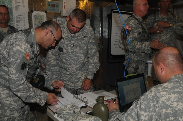 Maj. Gen. William Buckler, Jr., commander, 412th Theater Engineer Command, reviews unit training plan with Soldiers of 368th Engineer Battalion, 302nd Maneuver Enhancement Brigade, at Warrior Exercise, Fort McCoy, June 19, 2012. The 412th command team spent three days observing troops in action and engaging with commanders about critical training objectives and strategies necessary to improve readiness levels and to meet Army Force Generation requirements. More than 1,100 Soldiers from 412th downtrace units were at Fort McCoy for extended combat training.