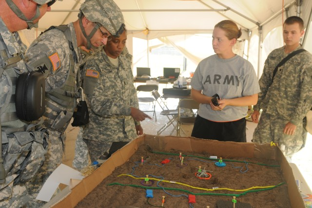 Maj. Gen. William Buckler, Jr., commander, 412th Theater Engineer Command, checks out a sandbox illustration as company leaders brief plan details at Warrior Exercise, Fort McCoy, June 19, 2012. The 412th command team spent three days observing troops in action and engaging with commanders about training standard, objectives and strategies necessary to improve readiness levels and to meet Army Force Generation requirements. More than 1,100 Soldiers from 412th downtrace units were at Fort McCoy for extended combat training.