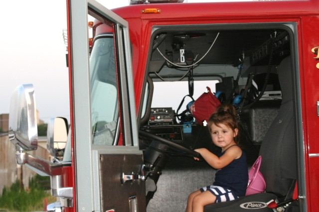 A young girl tries out the driver's seat of a Rock Island Arsenal, Ill., fire truck. Firefighters provided safety reminders to children who came out to watch the Arsenal's Red, White and Boom fireworks display on July 3. About 200 people gathered on the lawn near the Colonel Davenport house to watch the event. (Photo by Dan Carlson, ASC Public Affairs)