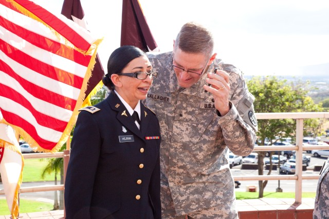 HONOLULU - Newly promoted Maj. Rhine Hejran (left), deputy chief of Inpatient Psychiatric Service, Tripler Army Medical Center, and Brig. Gen. Keith Gallagher, commander, Pacific Regional Medical Command and TAMC, talk to Hamed, Hejran's brother, on the phone after her promotion ceremony, June 12, at TAMC. Lt. Gen. Patricia Horoho, U.S. Army Surgeon General and commander, U.S. Army Medical Command, gave remarks at the ceremony and pinned Hejran along with Gallagher.