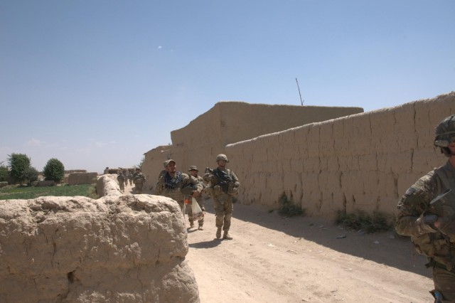 Members of the 3rd Platoon, Bravo Company, 5th Battalion, 20th Infantry Regiment, walk through the village of Pankilla in Zharay district, Afghanistan, June 29, 2012. This street connects the entire town and was previously one you could not travel on without a gun battle.
