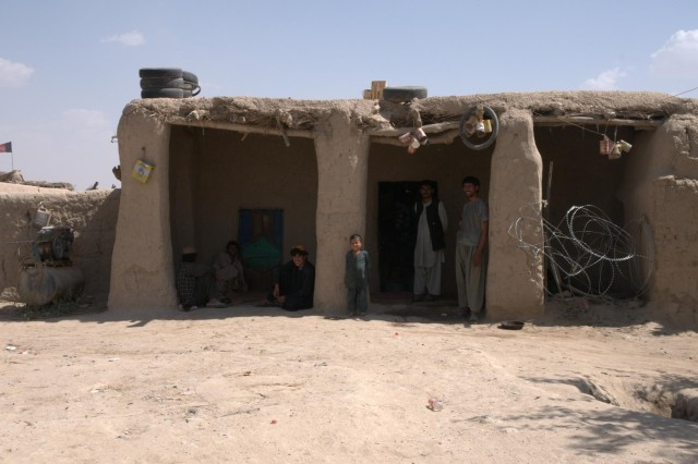 The shop owner and his family look out from their store, June 29, 2012, in Pankilla village, Afghanistan. The store, the only one in the village, used to be closed. Increased security has allowed them to return to work and the shop remains open.