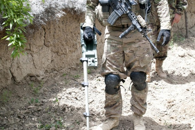 Staff Sgt. Antonio Barajas, 3rd Platoon, Battle Company, 5th Battalion 20th Infantry Regiment, Task Force 1st Squadron 14th Cavalry Regiment, uses a Gizmo to search for weapons caches in an orchard outside the village of Sowkray Tangay, Afghanistan, May 7, 2012. The Gizmo is a handheld metal detector that uses metal detection technology to locate metallic threats such as mines and caches.