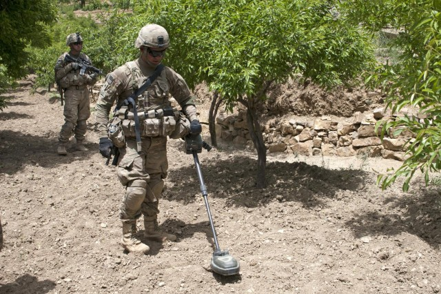 Pfc. Nikko Williams, 3rd Platoon, Battle Company, 5th Battalion 20th Infantry Regiment, Task Force 1st Squadron 14th Cavalry Regiment, uses a Minehound to search for weapons caches in an orchard outside the village of Sowkray Tangay, Afghanistan, May 7, 2012. The Minehound is a handheld detector that uses ground penetrating radar and metal detection technology which gives it the ability to detect deep buried, low metallic threats such as mines and caches.