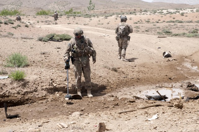 Staff Sgt. Anthony Shaw (left), 787th Ordnance Company, 3rd Ordnance Battalion, uses a VMR-2 MineHound to search for possible secondary improvised explosive devices following an earlier incident. The MineHound's ground penetrating radar allows operators to locate IEDs that may otherwise not be found by the naked eye.