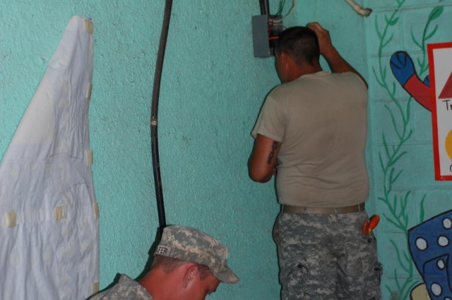 Missouri National Guard Spc. Adam Schafer (left), of the Perryville-based 800th Engineer Team (Haul), and Sgt. Joseph Broach, of the 220th Engineer Company, which is based out of Festus, Mo., work on fixing electrical wiring at Centenario Jose Trinidad Cabanas School in San Pedro Sula, Honduras, July 1, 2012. The Soldiers are in Honduras as part of U.S. Army South's Beyond the Horizon 2012 exercise, which combines military skills training with humanitarian aid missions.