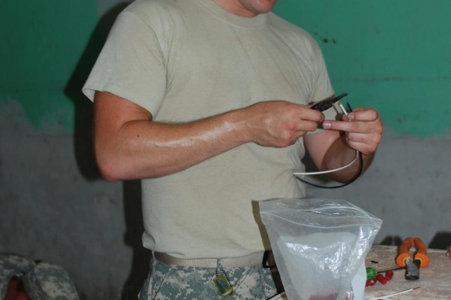Missouri National Guard Spc. Jesse Dean, of the 220th Engineer Company, which is based out of Festus, Mo., prepares a light fixture at Centenario Jose Trinidad Cabanas School in San Pedro Sula, Honduras, July 1. is in Honduras as part of U.S. Army South's Beyond the Horizon 2012 exercise, which combines military skills training with humanitarian aid missions.