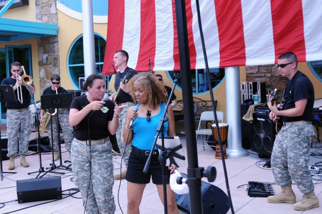"""Sgt. Sherri Wornath of the 100th Army Band out of Fort Knox, Ky., is joined by a member of the audience in singing Aretha Franklin's """"Think"""" during Fourth of July festivities in Gatlinburg, Tenn. The 100th marched in the 37th Annual Fourth of July midnight Parade which kicked off at 12 a.m., marking it as the first, chronologically, of the nation's celebrations, a distinction the City of Gatlinburg maintains with pride. On July 3rd, some of the band's Music Performance Teams, such as the Jazz and Rock Bands and the Brass Quintet played in front of the City's Aquarium. The entire band also played a patriotic concert on the evening of the 4th leading into the traditional fireworks show."""