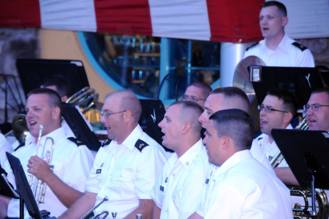 "Soldiers of the 100th Army Band sing ""The Dogfaced Soldier"" during their evening concert on July 4 in Gatlinburg, Tenn. The 100th marched in the 37th Annual Fourth of July Midnight Parade which kicked off at 12 a.m., marking it as the first, chronologically, of the nation's celebrations, a distinction the City of Gatlinburg maintains with pride. On July 3rd, some of the band's Music Performance Teams, such as the Jazz and Rock Bands and the Brass Quintet played in front of the City's Aquarium. The entire band also played a patriotic concert on the evening of the 4th leading into the traditional fireworks show."