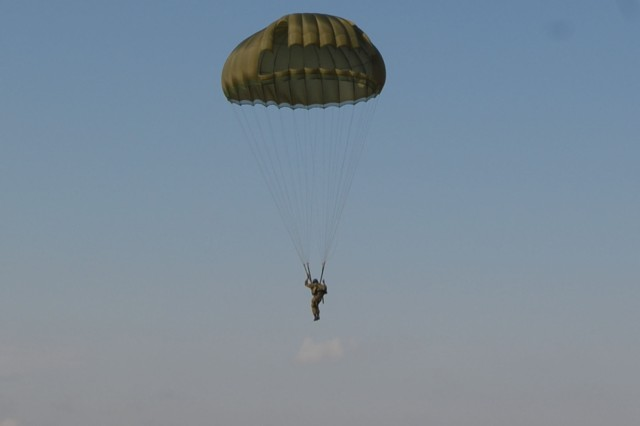 A U.S. Special Forces Soldier watches while a Botswana Defense Force Special Forces soldier prepares to land in the drop zone. The combined U.S. Special Forces and BDFSF parachute jump was in the final week of Exercise Eastern Piper 12.