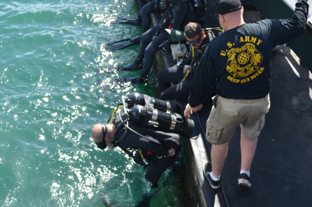 Sgt. 1st Class Beau Woodcox (Master Diver), 1st Sgt, 7th Dive Detachment, 65th Engineer Battalion, 130th Engineer Brigade, 8th Theater Sustainment Command, supervises entry of divers into the water next to the USS Arizona Memorial at Pearl Harbor, Hawaii, June 28, 2012.