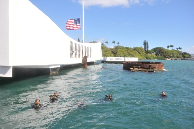 Divers from the 7th Dive Detachment, 65th Engineer Battalion, 130th Engineer Brigade, 8th Theater Sustainment Command, prepare to head beneath the waters of Pearl Harbor, Hawaii, to inspect and tour the USS Arizona Memorial, June 28, 2012.
