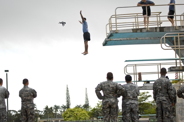Sgt. Joseph Smith, arms room NCO for Headquarters and Headquarters Company, 8th Special Troops Battalion, 8th Theater Sustainment Command, shows the improper way to jump off of the diving platform with a weapon during his unit's annual drown proofing training at Richardson Pool on Schofield Barracks, June 22 and 29.