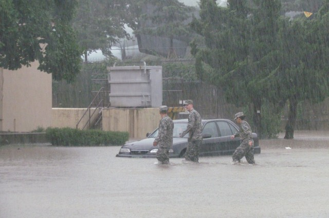 Soldiers on U.S. Army Garrison Yongsan weather the storm and get across the installation by foot during a flooding. These effects have been visible on garrison especially in certain areas such as the Moyer Recreation Center, which in past years has experienced flooding. (Courtesy Photo)